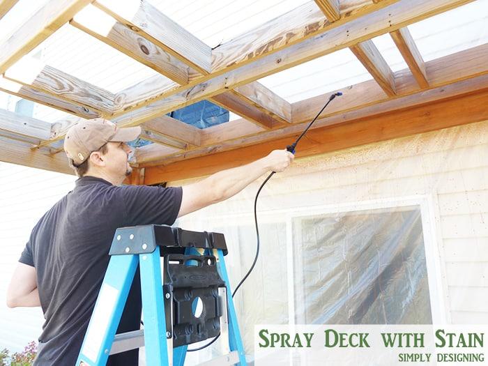 spraying stain on deck