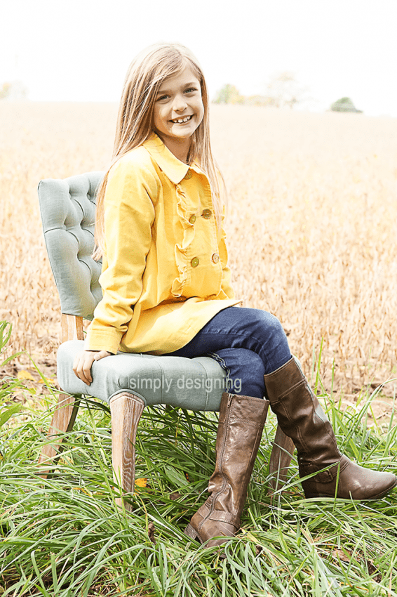 Photo of Girl in a yellow jacket, jeans and boots on Chair in Field