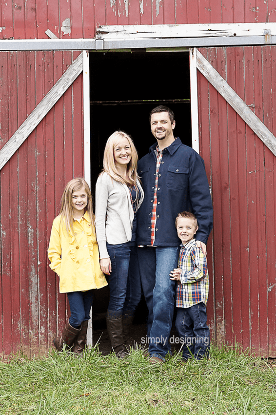 Family Photo of parents Standing in front of partially opened Barn Door with kids on the sides in front of barn doors
