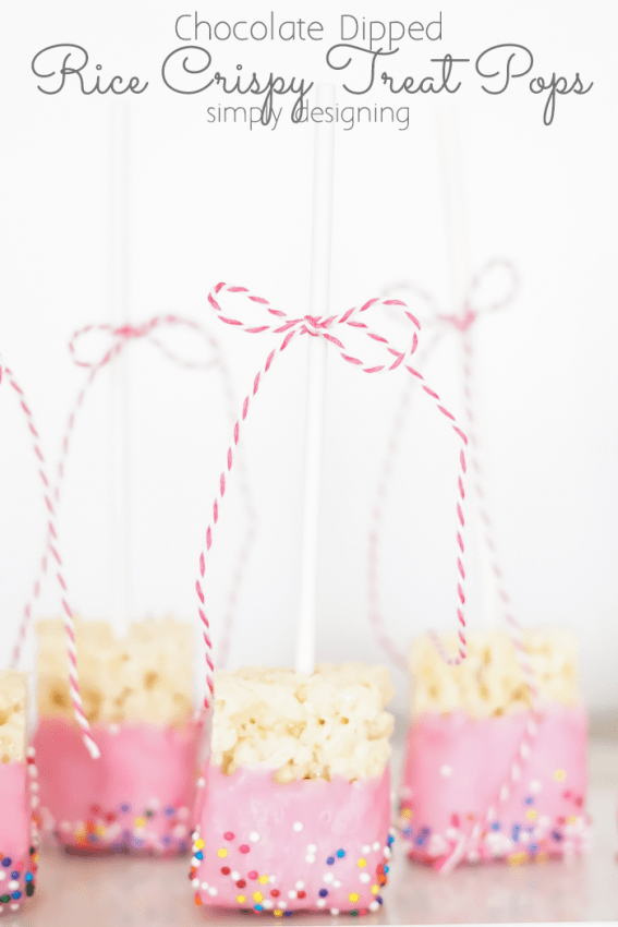 close up of pink Chocolate Dipped Rice Crispy Treat Pops standing up with sticks in the air and a pink twine bow tied to the stick
