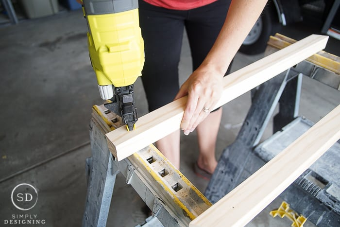 Using a Nail Gun to add a couple brad nails to hold the post boards together for the DIY Baby Gate