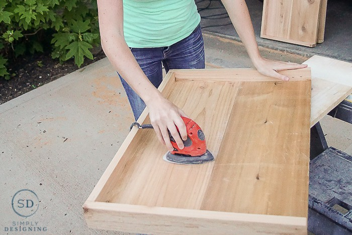 Ashley from Simply Designing using an electric sander to sand the shelves down for the printer table