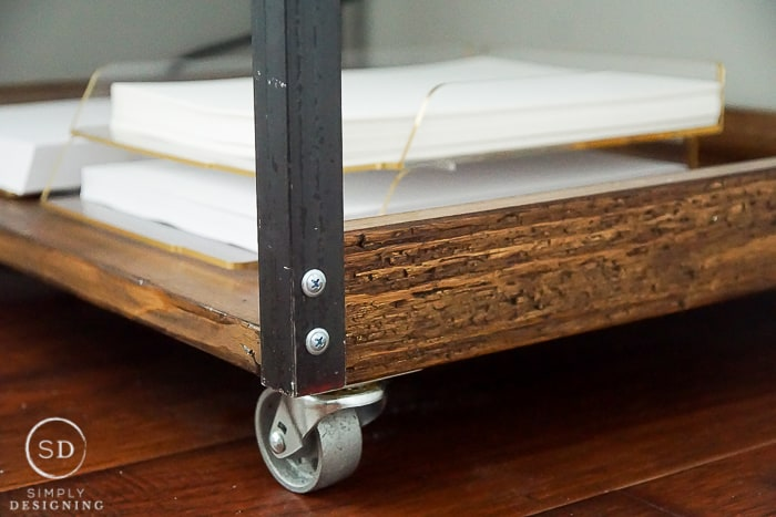close up photo of wheels and bottom shelf of printer table cart