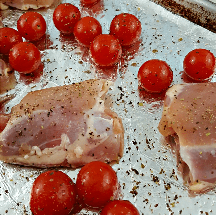 Simple to prep Sheet Pan Caprese Chicken - chicken breasts on a tinfoil lined sheet pan with tomatoes sprinkled with olive oil and Italian seasoning.