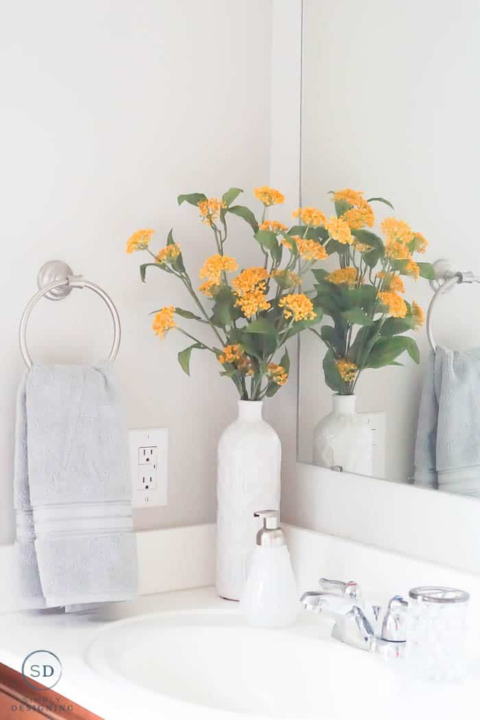 Gray hand towel and yellow flowers in a white vase