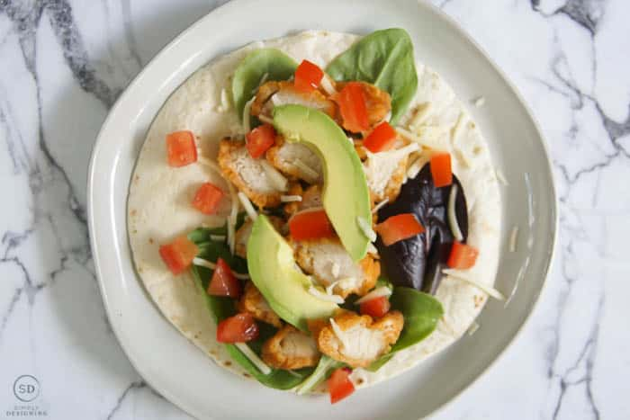 tortilla with lettuce and chicken and cheese and avocado and tomato