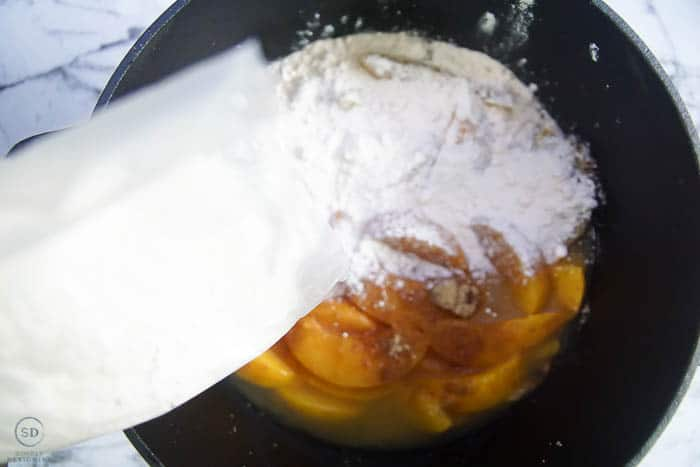 sprinkle cake mix on peaches for peach cobbler with cake mix