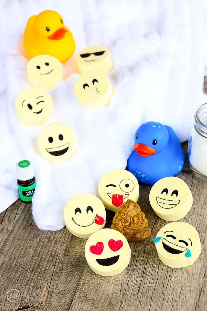 All the different kids bath bombs, this bath bomb recipe makes emoji faced tablets that you can drop in the bath. The finished bath bombs are surrounded by other bath essentials like towels and bath toys for kids.