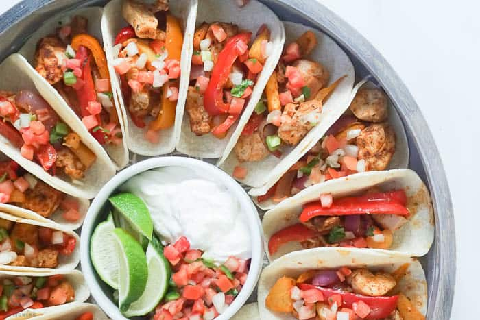 one pan chicken fajitas with toppings of sour cream pico and lime