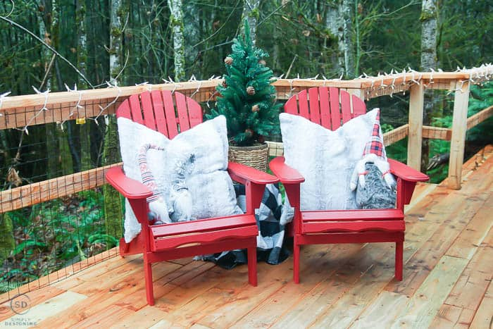 adirondack chairs painted red and decorated for christmas