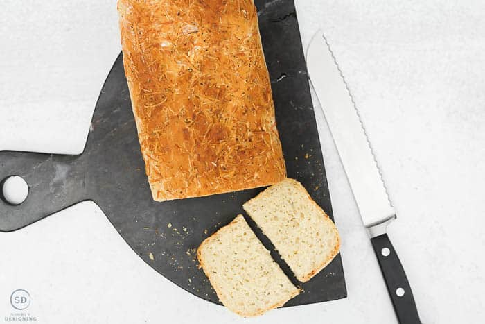 this herb artisan bread is so simple to make - sliced and cut bread on black marble cutting board
