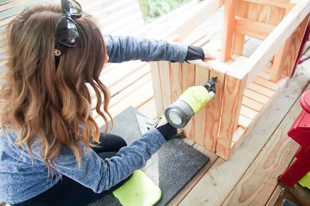 using nail gun to attach siding boards to pet house