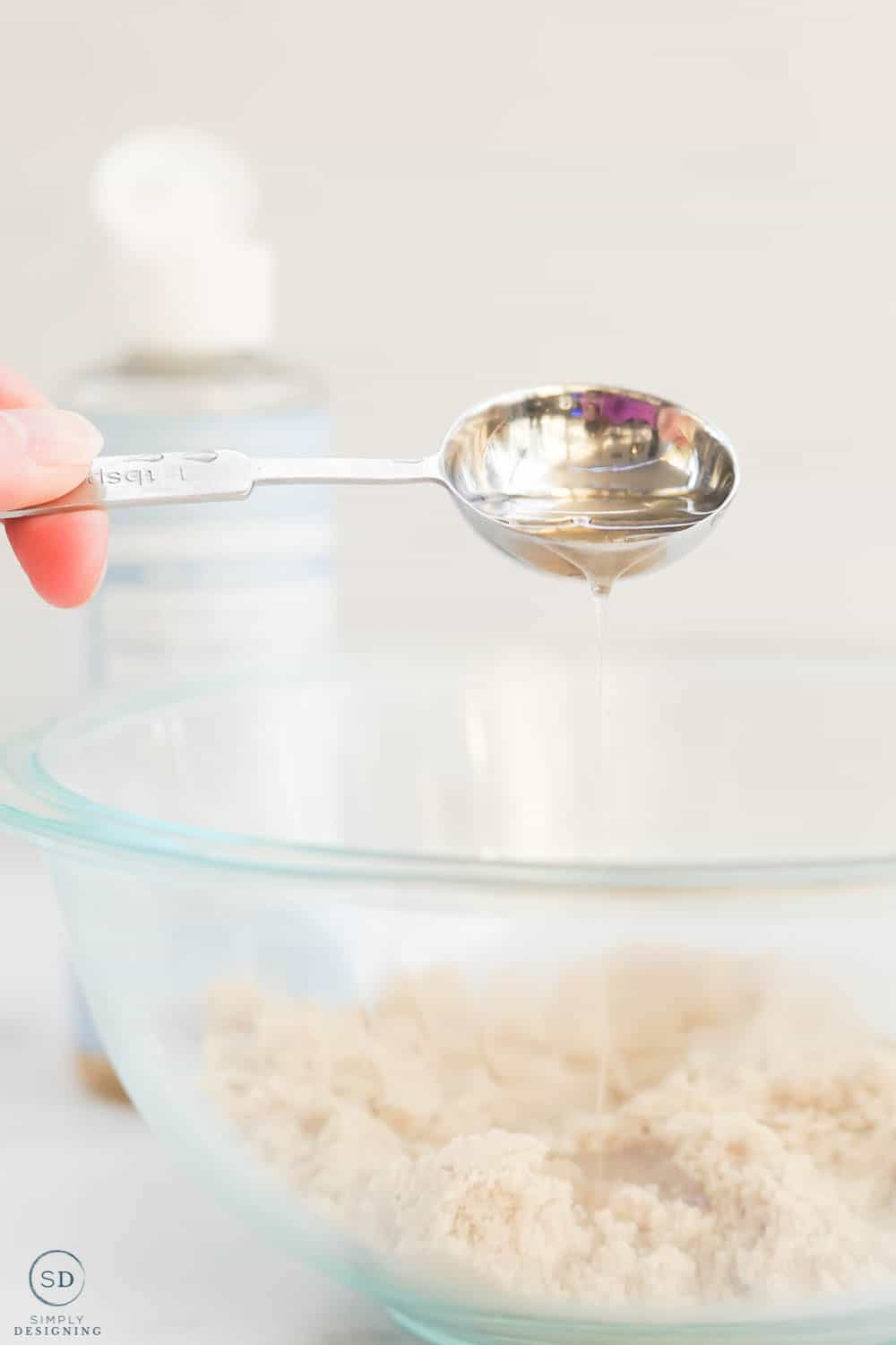 using a measuring spoon to pour castile soap into brown sugar