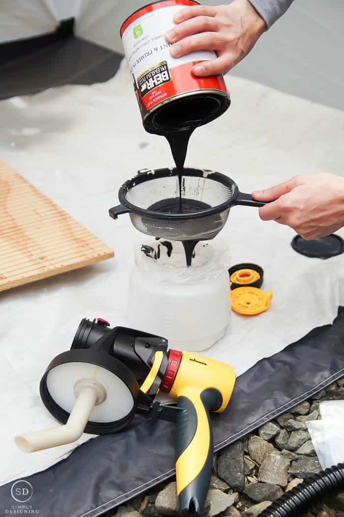 pouring paint through a strainer and into a paint sprayer