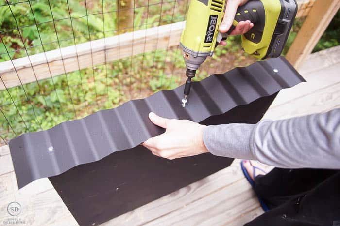 using drill to screw corrugated metal to roof for bat box