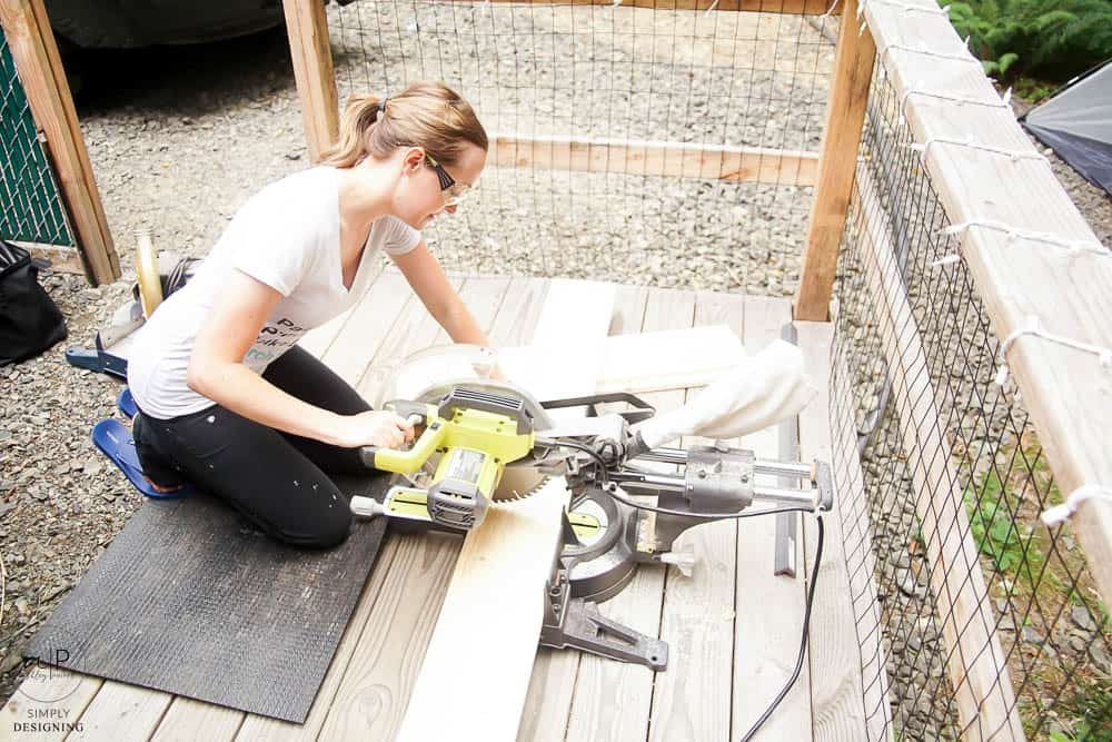 woman cutting wood with a compound miter saw