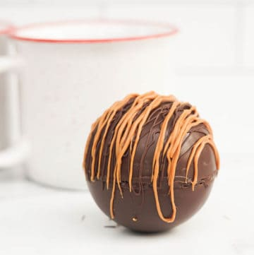 caramel hot cocoa bomb recipe with white mugs in the background